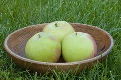 3 зеленых сочных яблока в деревянной плите на траве Стоковое Изображение RF