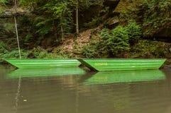 2 зеленых шлюпки плавая над телом воды Стоковые Изображения