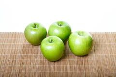 4 зеленых яблока на бамбуковой циновке Стоковые Изображения