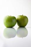 2 зеленых яблока на белизне от стороны с вертикалью отражения Стоковые Фото