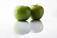 2 зеленых яблока на белизне от стороны с отражением Стоковое Изображение