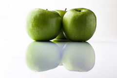 3 зеленых яблока на белизне от стороны с отражением Стоковая Фотография RF