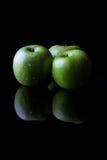 3 зеленых яблока на черноте от стороны с вертикалью отражения Стоковые Изображения