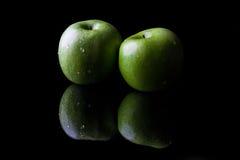 2 зеленых яблока на черноте от стороны с отражением Стоковое Изображение