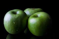 3 зеленых яблока на черноте от стороны Стоковое Изображение