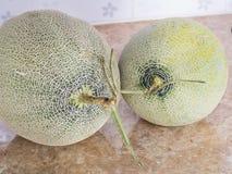 2 зеленых японских дыни на счетчике в кухне Стоковые Фотографии RF