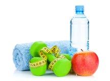 2 зеленых dumbells, рулетка, яблоко и бутылки с водой Стоковое фото RF