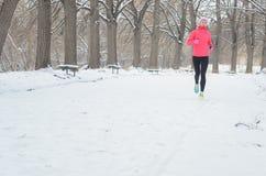 Зима бежать в парке: счастливый бегун женщины нагревая и работая перед jogging в снеге, внешнем спорте и фитнесе Стоковое Изображение RF