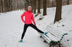 Зима бежать в парке: счастливый бегун женщины нагревая и работая перед jogging в снеге, внешнем спорте и фитнесе Стоковая Фотография
