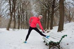 Зима бежать в парке: счастливый бегун женщины нагревая и работая перед jogging в снеге Стоковые Изображения RF