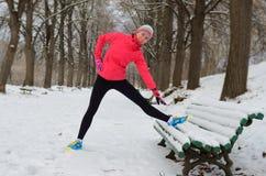 Зима бежать в парке: счастливый бегун женщины нагревая и работая перед jogging в снеге Стоковое фото RF