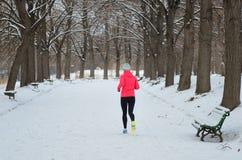 Зима бежать в парке: счастливый бегун женщины jogging в снеге, внешнем спорте и фитнесе Стоковые Фотографии RF
