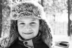 Зима в древесинах мальчик в крышке с earflaps Почерните a стоковые изображения