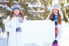 Зима. Девушки с пустым знаменем. Стоковые Фото