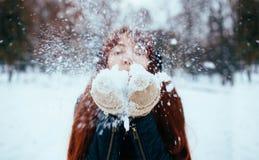 Зима Женщина с ухом красных волос нося muffs дуть на снеге в руках стоковые фото