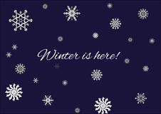Зима здесь помечает буквами вектор с снежинками и голубой предпосылкой Стоковая Фотография