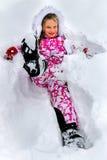 Зима маленькой девочки нося одевает лежать в глубоком снеге Стоковые Изображения RF