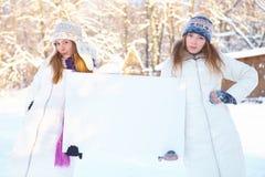 Зима. Молодые женщины с пустым знаменем. Стоковые Фотографии RF