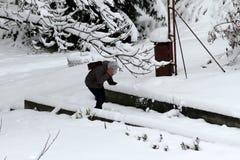 Зима Огромные опасные сосульки льда висят над здоровьем угрозой улицы и жизнью людей вися от крыши здания Стоковая Фотография