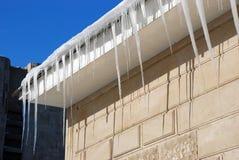 Зима Огромные опасные сосульки льда висят над здоровьем угрозой улицы и жизнью людей вися от крыши здания с c Стоковые Фото