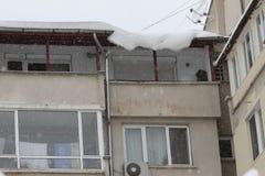 Зима Огромный опасный вид снега льда над здоровьем угрозой улицы и жизнью людей вися от крыши здания с c Стоковое Изображение RF