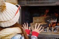 Зима дома, милая маленькая девочка сидя около места огня Стоковое фото RF