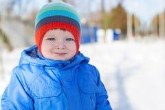 Зима тепло одела мальчика идя на снежную улицу стоковые изображения rf