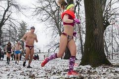 Зима участвует в гонке в их нижнем белье через древесины в снеге Стоковая Фотография