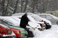 Зима Человек с веником очищает автомобиль от снега на улице после большой пурги в городе, всех автомобилях под снегом, ледистых д стоковое изображение rf
