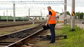 Злий вождь на железной дороге проверяет механизм железной дороги переключателя и screams на телефоне сток-видео