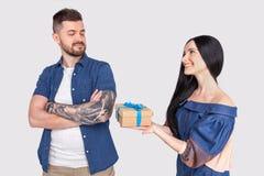 Злодействованный парень Девушка дает подарок парню который обиден ей одетый в случайной одежде стойка перед серым цветом стоковое фото rf