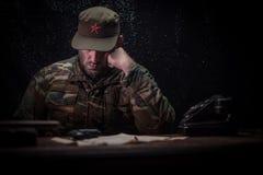 Злой диктатор сидя на таблице Сердитое коммунистическое общее усаживание на управлении или кубинськом командире в темной комнате стоковое фото rf