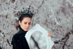 Злой ферзь с волшебным зеркалом в стране чудес зимы стоковое фото rf