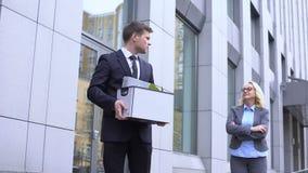 Злорадствуя зрелая женщина смотря уволенного молодого работника покидая офис, конфликт акции видеоматериалы