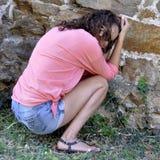 Злоупотребленная и устрашенная женщина сидя в угле покинутого Стоковые Фотографии RF