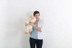 Злющая женщина сдерживает ее кота игрушки плюша для уха, серой предпосылки студии смешная ситуация Стоковое Изображение RF