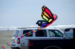 Змей бабочки над тележкой на берегах океана Стоковые Фото