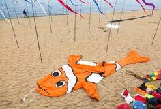 Змей воздуха в форме большой оранжевой рыбы лежит на песочном bea Стоковые Фотографии RF