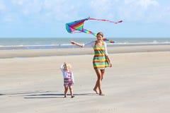 Змей летания матери и ребенка на пляже Стоковое фото RF