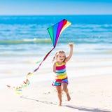 Змей летания ребенка на тропическом пляже Стоковое Изображение