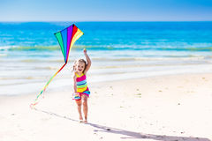 Змей летания ребенка на тропическом пляже Стоковые Изображения