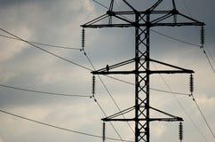 Змей хищной птицы черный сидя на заржаветых лучах металла башни линии электропередач против облачного неба Стоковое Изображение RF