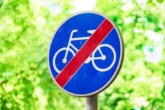 Знаки для велосипедистов, дорожного знака против предпосылки зеленых деревьев стоковые изображения rf