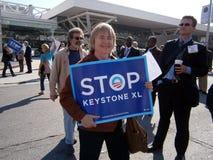 Знаки женским владением протестующего большие говоря 'KEYSTONE XL СТОПА' на h Стоковое фото RF