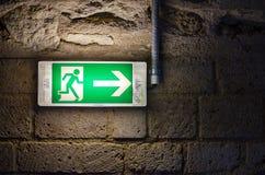 Знак аварийного выхода салатовый на кирпичной стене в темноте Стоковые Фотографии RF