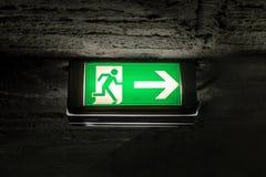 Знак аварийного выхода салатовый на потолке кирпича в темноте Стоковая Фотография