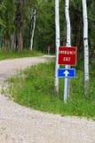 Знак аварийного выхода вдоль проселочной дороги при другой такой же знак запачканный на заднем плане Стоковые Фотографии RF