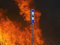 Знак автобусной остановки и пламени огня за им Стоковая Фотография