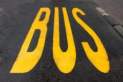 Знак автобусной остановки с желтой краской на асфальте Стоковые Фотографии RF