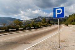Знак автостоянки около дороги, горы Стоковое Фото